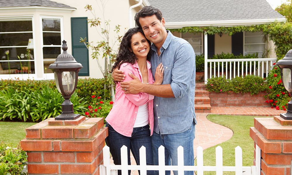 Young Hispanic couple embracing in front of home