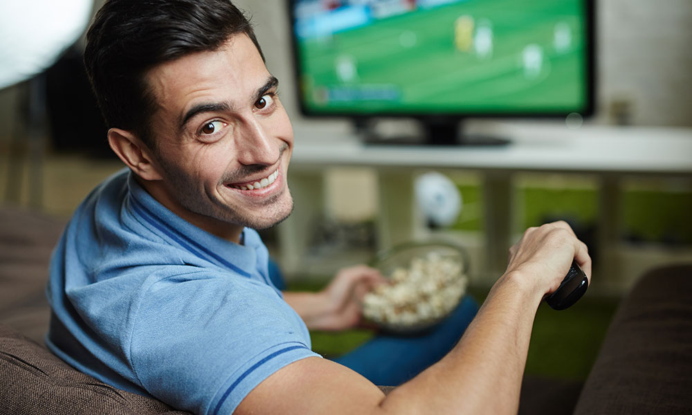 Smiling man watching sports on TV